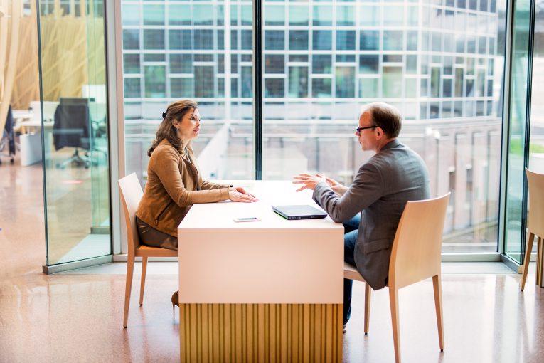 Vrouw en man aan tafel tegenover elkaar